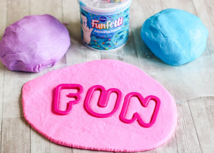Pink edible frosting play dough with pink cookie cutter letters spelling,