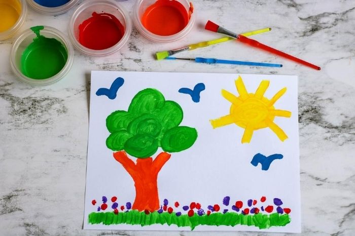 Kid's painting of a tree and a sun with birds with homemade paint.