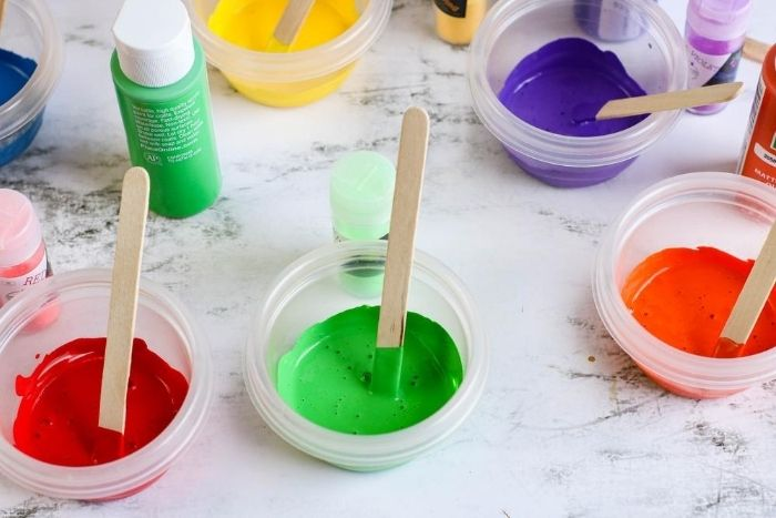 Red, green, and orange paint in clear bowls with small wooden popsicle sticks in each bowl.