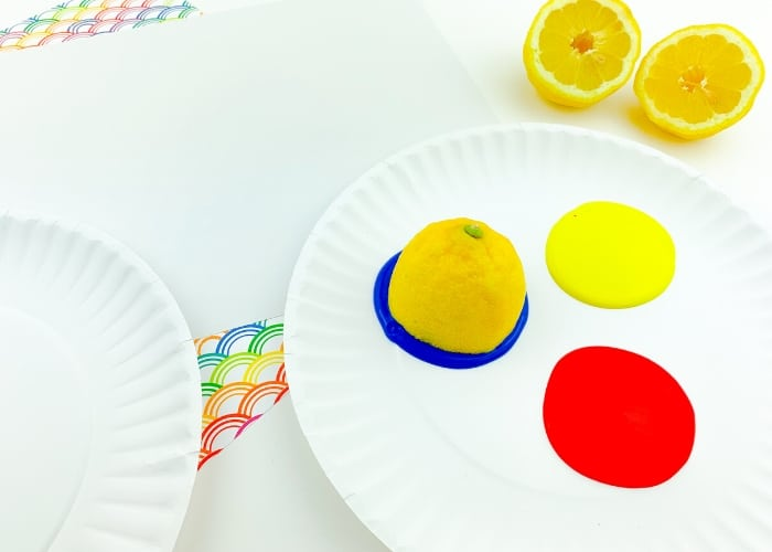 Half a lemon sitting in blue paint on a paper plate with red and yellow paint.