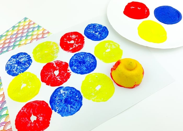 Painting with lemons on a piece of paper using red, blue, and yellow paint.