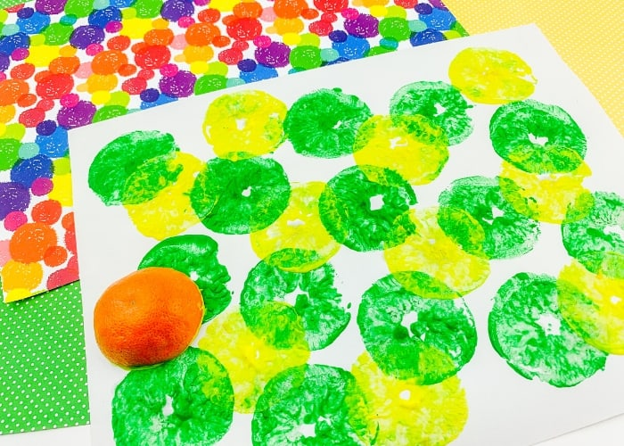 Painting with half an orange with green and yellow paint on white paper.