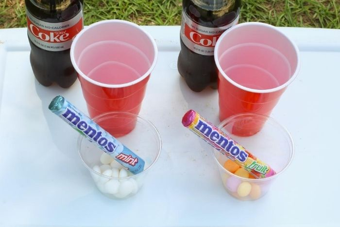 Fruit and Mint Mentos candies in clear cups next to red plastic cups.