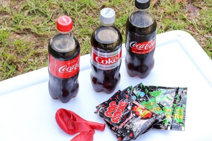 Plastic bottles of Coke on a table with packages of pop rocks and balloons.