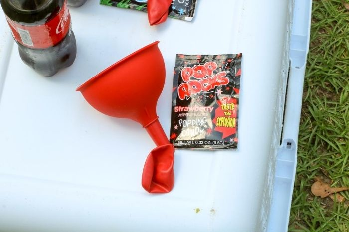 A balloon on the end of a plastic funnel nect to a package of red pop rocks.