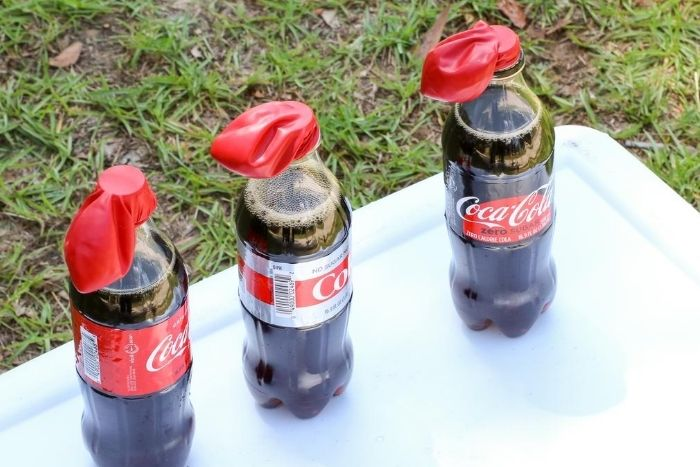 The different types of bottles of Coke with red balloons over the openings for a Pop Rocks science experiment.