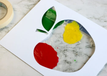 Overhead shot of an apple cutout sitting over a zip-lock bag of paint for mess free finger painting.