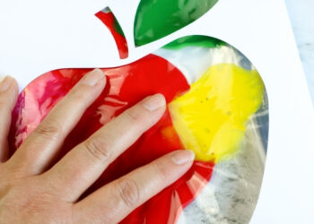 A child's hand doing the Apple Theme Mess Free Finger Painting in a Bag activity.