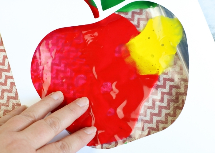 A child's hand doing the Apple Theme Mess Free Finger Painting activity.