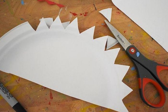 A folded paper plate with triangles cut out of the rounded edge.
