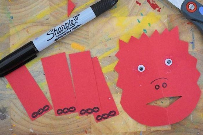 The arms and face for the dinosaur craft made out of construction paper.