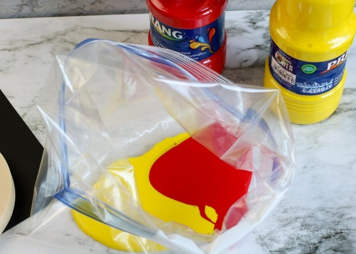 Red and yellow paint in an open gallon zip top bag.