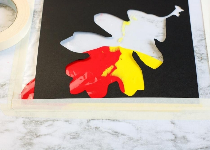 Red and yellow paint in a leaf shape for sensory painting.
