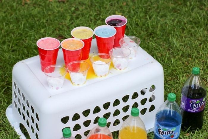 Colorful soda with food coloring in cups next to cups of mentos and baking soda.
