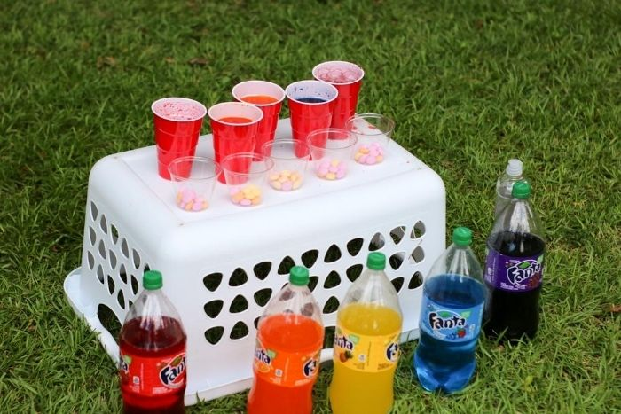 Rainbow soda science experiment ingredients mixed in cups with cups of mentos in front of them.