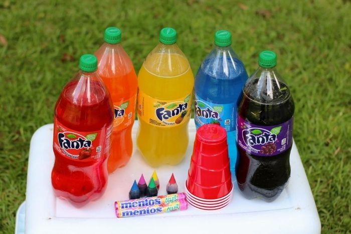 Soda, mentos, food coloring and cups set on top of an upside down laundry basket.