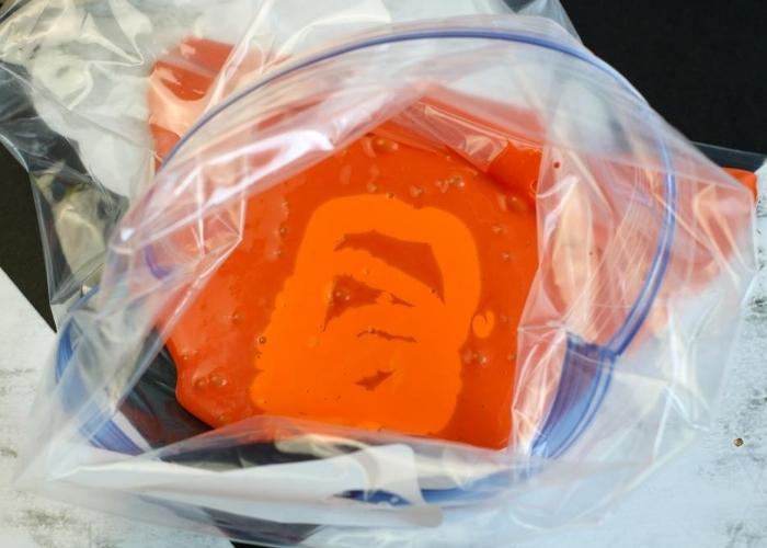 Overhead shot of orange tempura paint in a zip-lock bag.