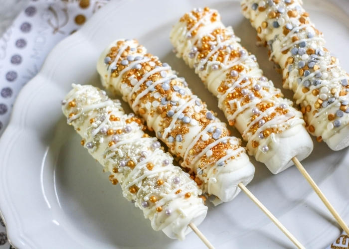 Overhead shot of finished New Years Marshmallow Pops on a white serving plate.