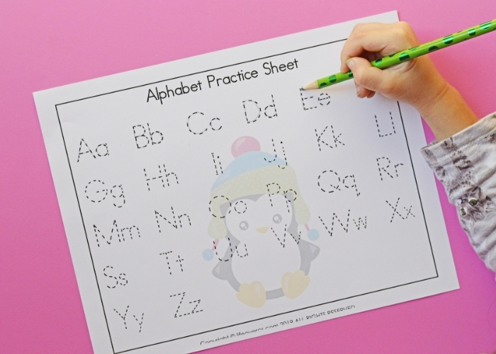 A child completing a penguin themed alphabet practice sheet.