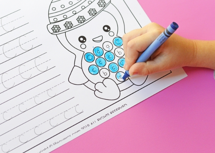 Up close picture of a child coloring in the letter