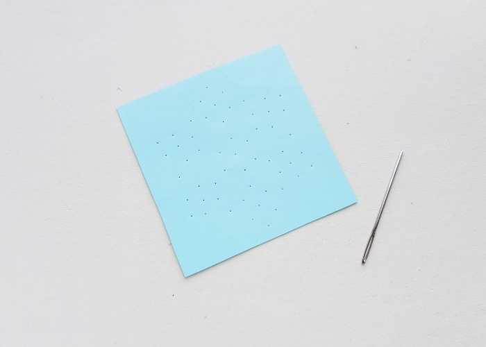 A needle sitting next to a square piece of construction paper with holes in it for the snowflake stitching craft.