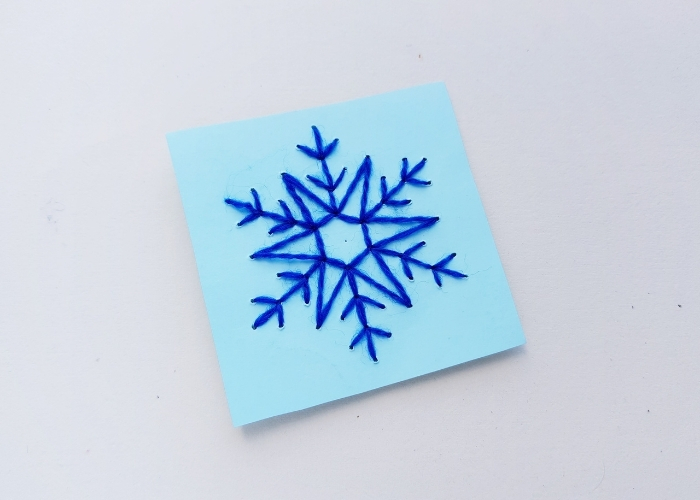 Overhead shot of the finished Snowflake Stitching Fine Motor Craft on a white background.