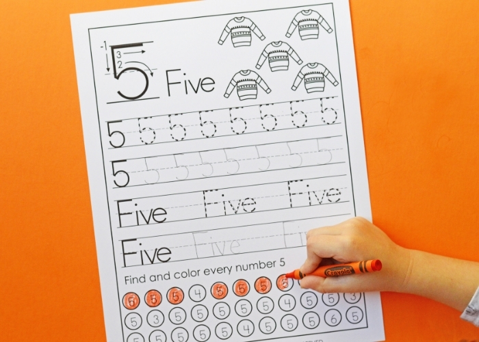 Overhead shot of a child completing a winter theme number worksheet for the number 5.