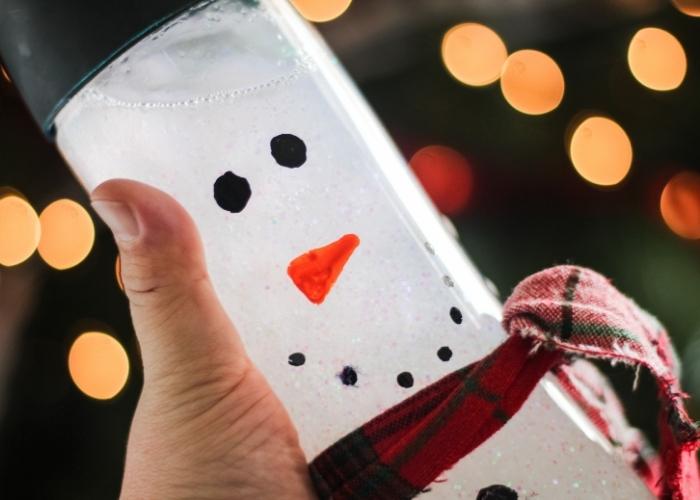 A child's hand holding the snowman sensory bottles DIY.