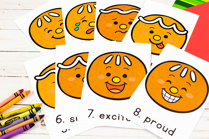 The gingerbread face images for the Write the Room Gingerbread Emotions activity laid out next to some crayons.