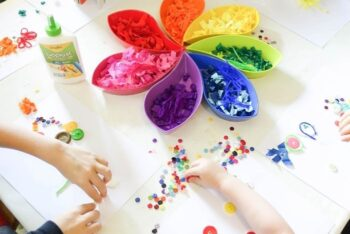 Kids creating a color craft with various colored craft paper and buttons.