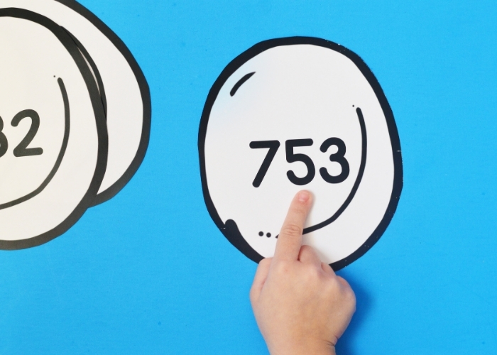 A kid pointing at the tenths place on a Snowball Place Value Practice printable.