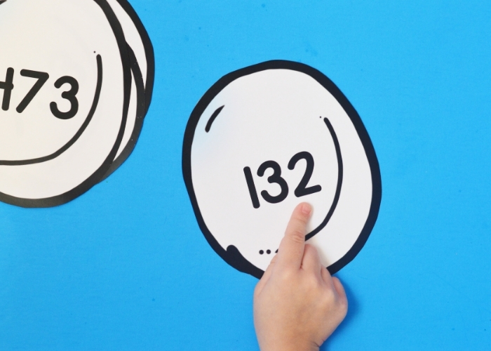 A kid pointing at the ones place on a Snowball Place Value Practice printable.