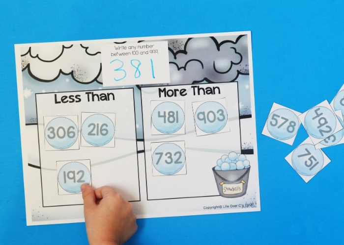 A child using the Snowball Math Game less than / more than activity.
