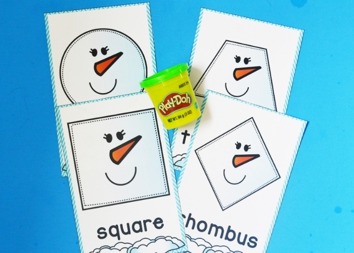 A tub of playdough sitting between free printable snowman shape playdough mats.