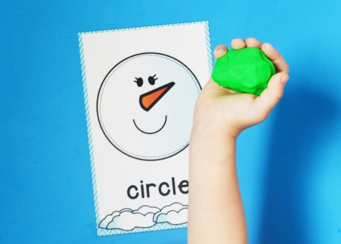 A kid holding a ball of green playdough over a snowman circle shape playdough mat.