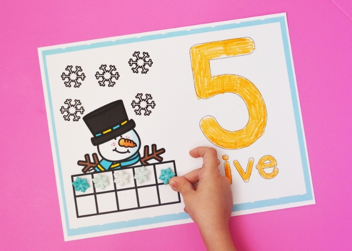 """A child placing a snowflake on a Snowman Ten Frame Number Mat for the number """"5""""."""
