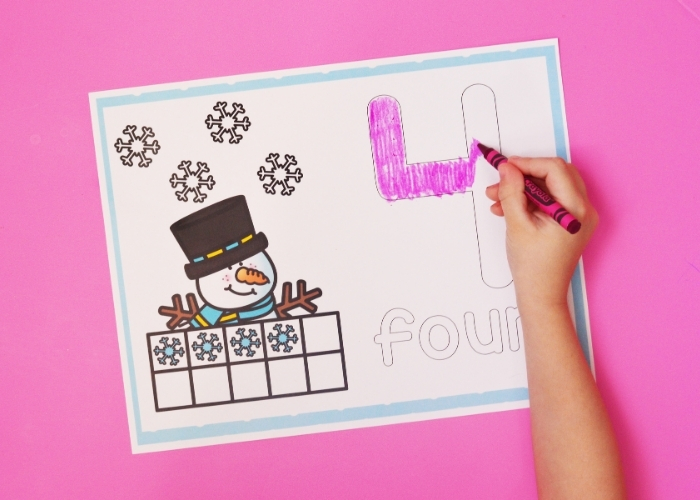 """A kid coloring in the number """"4"""" on a Snowman Number Mat."""