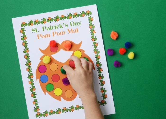 A child placing a green pom pom on a St Patricks' Day color matching pom pom mat.