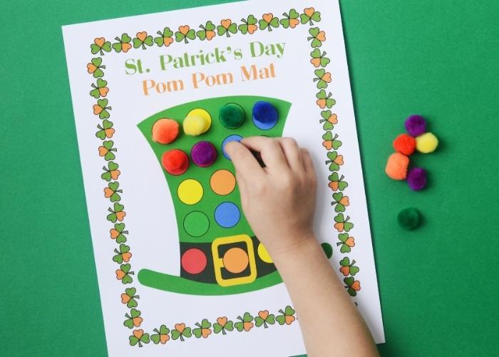 A child placing a blue pom pom on a St Patricks' Day color matching pom pom mat.