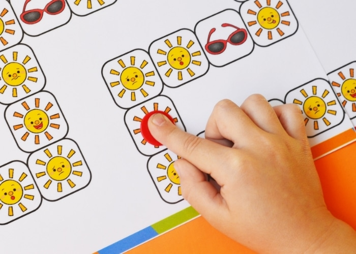 Close up of a child moving a token on the sun emotions board game.