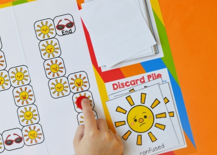 Overhead view of a child moving a token on the sun emotions board game.
