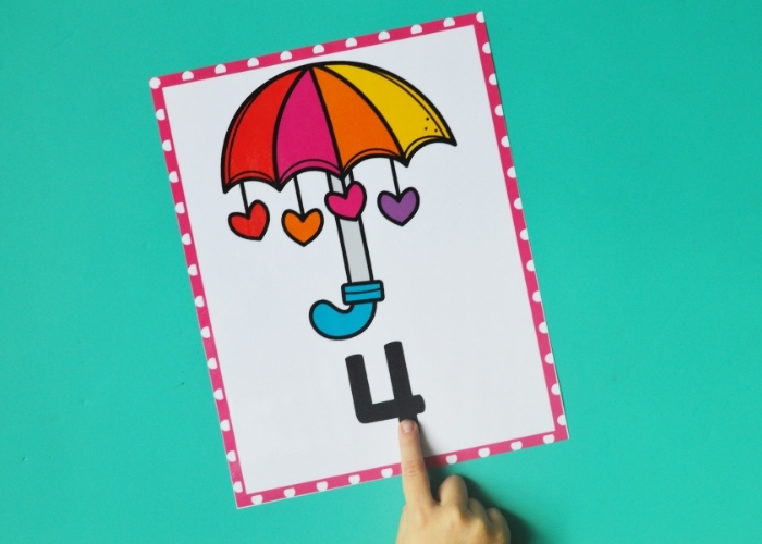 A child's hand pointing at the number 4 on a Valentine's themed number poster.