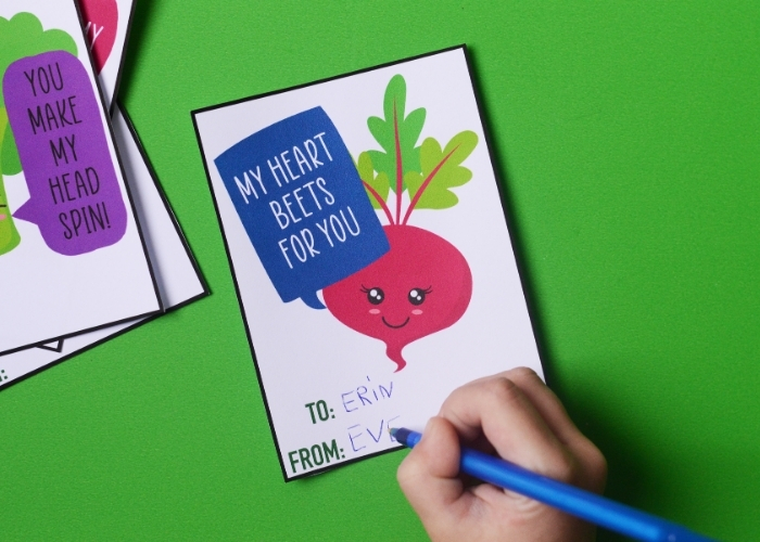 "A child writing on a ""My heart beets for you"" veggie valentine card."