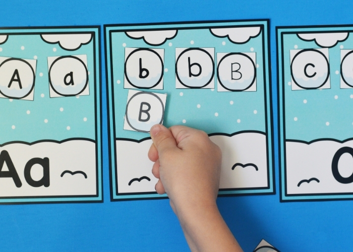 """A child's hand placing an uppercase """"B"""" on the Winter Alphabet Sort Activity."""
