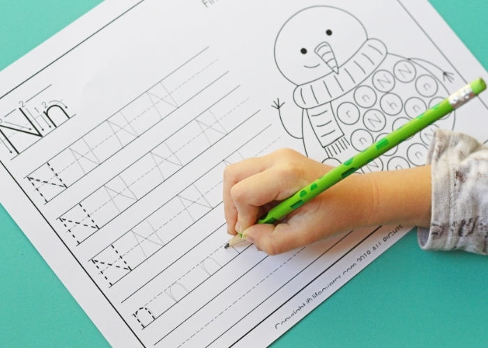 Child's hand practicing writing letters on a printable handwriting worksheet.