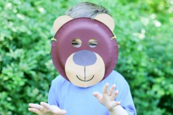 A child wearing a brown bear paper plate mask craft.