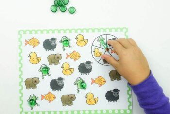 A child playing the animal colors spin game from the animal theme preschool lesson plan.