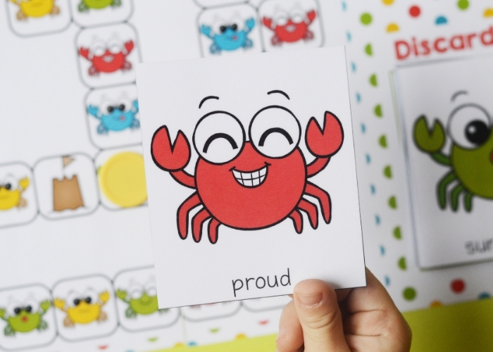Child's hand holding a proud crab emotions card.