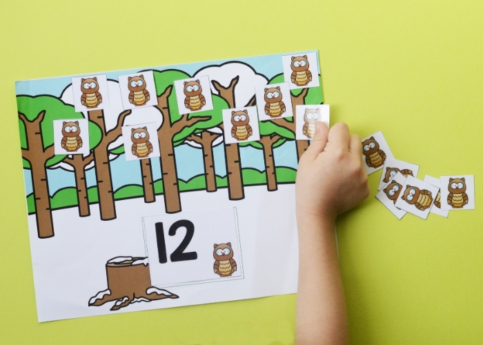 A child placing owl counting tokens on a forest animal counting activity mat for the number 12.