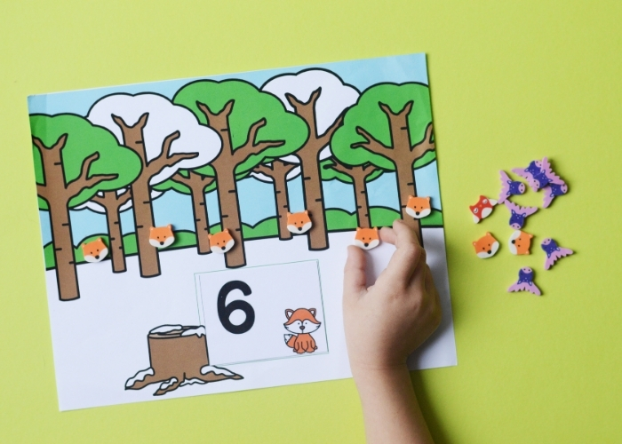 A child counting to 6 with the fox forest animal mini eraser counting activity mat.